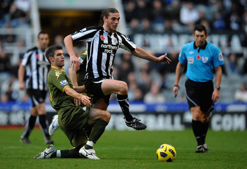 NEWCASTLE UPON TYNE, ENGLAND - NOVEMBER 13: Andy Carroll of Newcastle United battles for the ball with Aaron Hughes of Fulham during the Barclays Premier League match between Newcastle United and Fulham at St James' Park on November 13, 2010 in Newcastle