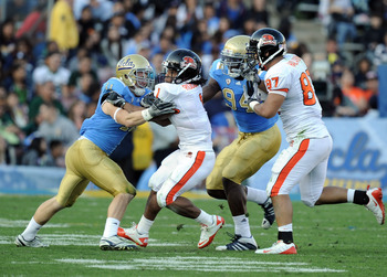 PASADENA, CA - NOVEMBER 06:  Jacquizz Rodgers #1 of the Oregon State Beavers runs between Sean Westgate #11 and Owamagbe Odighizuwa #94 of the UCLA Bruins as Joe Halahuni #87 attempts to block at the Rose Bowl on November 6, 2010 in Pasadena, California.