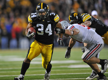 IOWA CITY, IA - NOVEMBER 20:  Running back Marcus Coker #34 of the University of Iowa Hawkeyes drives the ball past linebacker Ross Homan #51 of the Ohio State Buckeyes during the second half of play at Kinnick Stadium on November 20, 2010 in Iowa City, I