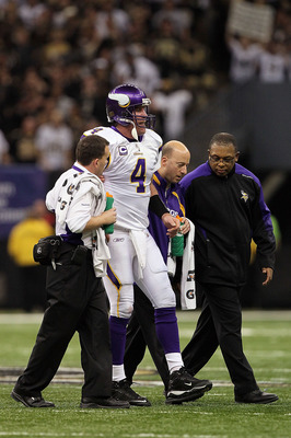NEW ORLEANS - JANUARY 24:  Brett Favre #4 of  the Minnesota Vikings is helped off the field by medical staff after getting injured on a play against the New Orleans Saints during the NFC Championship Game at the Louisiana Superdome on January 24, 2010 in
