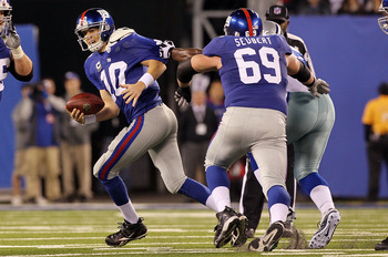 EAST RUTHERFORD, NJ - NOVEMBER 14:  Eli Manning #10 of the New York Giants tries to run the ball against the Dallas Cowboys on November 14, 2010 at the New Meadowlands Stadium in East Rutherford, New Jersey. The Cowboys defeated the Giants 33-20.  (Photo