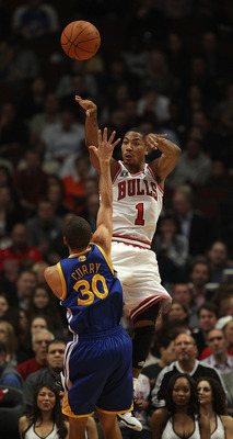 CHICAGO - NOVEMBER 11: Derrick Rose #1 of the Chicago Bulls leaps to pass the ball over Stephen Curry #30 of the Golden State Warriors at the United Center on November 11, 2010 in Chicago, Illinois. NOTE TO USER: User expressly acknowledges and agrees tha