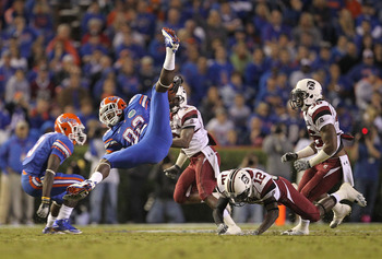 GAINESVILLE, FL - NOVEMBER 13: D.L. Moore #82 of the Florida Gators is upended after a catch by C.C. Whitlock #12 of the South Carolina Gamecocks during a game at Ben Hill Griffin Stadium on November 13, 2010 in Gainesville, Florida.  (Photo by Mike Ehrma