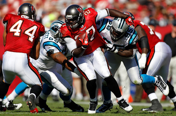 TAMPA, FL - NOVEMBER 14:  Running back LeGarrette Blount #27 of the Tampa Bay Buccaneers is tackled by defender Charles Johnson #95 of the Carolina Panthers during the game at Raymond James Stadium on November 14, 2010 in Tampa, Florida.  (Photo by J. Mer