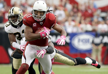 GLENDALE, AZ - OCTOBER 10:  Wide receiver Larry Fitzgerald #11 of the Arizona Cardinals runs with the football after a reception past Jabari Greer #33 of the New Orleans Saints during the NFL game at the University of Phoenix Stadium on October 10, 2010 i