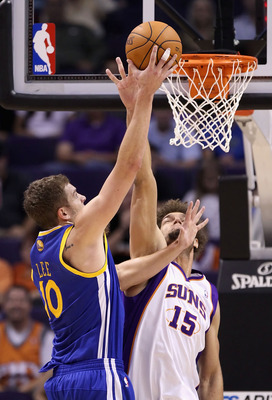 PHOENIX - OCTOBER 19:  David Lee #10 of the Golden State Warriors lays up a shot over Robin Lopez #15 of the Phoenix Suns during the preseason NBA game at US Airways Center on October 19, 2010 in Phoenix, Arizona. NOTE TO USER: User expressly acknowledges