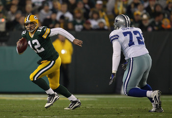 GREEN BAY, WI - NOVEMBER 07: Aaron Rodgers #12 of the Green Bay Packers runs out of the pocket while looking for a receiver pursued by Stephen Bowen #72 of the Dallas Cowboys at Lambeau Field on November 7, 2010 in Green Bay, Wisconsin. The Packers defeat