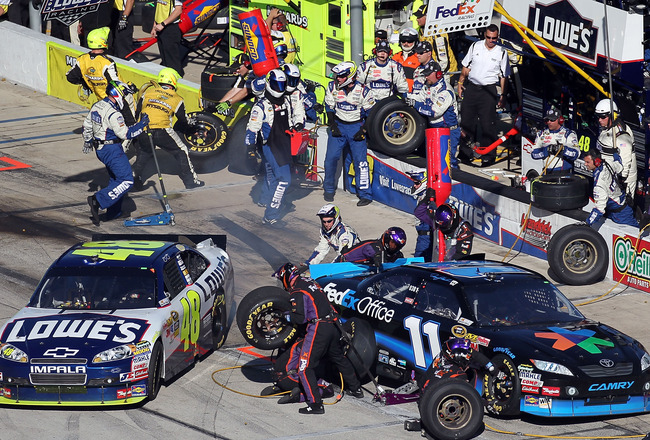 FORT WORTH, TX - NOVEMBER 07:  Jimmie Johnson, driver of the #48 Lowe's Chevrolet, pulls out of his pit as Denny Hamlin, driver of the #11 FedEx Office Toyota, makes a pit stop during the NASCAR Sprint Cup Series AAA Texas 500 at Texas Motor Speedway on N