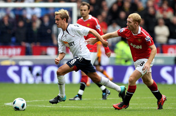 BOLTON, ENGLAND - SEPTEMBER 26:  Stuart Holden of Bolton Wanderers is challenged by Paul Scholes of Manchester United during the Barclays Premier League match between Bolton Wanderers and Manchester United at the Reebok Stadium on September 26, 2010 in Bo