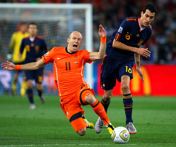 JOHANNESBURG, SOUTH AFRICA - JULY 11:  Arjen Robben of the Netherlands falls to the ground after being tackled by Sergio Busquets of Spain during the 2010 FIFA World Cup South Africa Final match between Netherlands and Spain at Soccer City Stadium on July