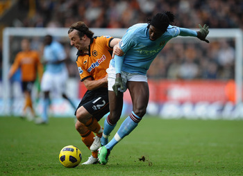 WOLVERHAMPTON, ENGLAND - OCTOBER 30:  Emmanuel Adebayor of Manchester City battles with Stephen Hunt of Wolves during the Barclays Premier League match between Wolverhampton Wanderers and Manchester City at Molineux on October 30, 2010 in Wolverhampton, E