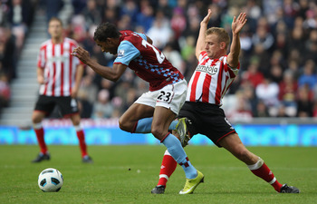 SUNDERLAND, ENGLAND - OCTOBER 23:  Habib Baye  of Aston Villa leaps over a challenge from Lee Cattermole of Sunderland during the Barclays Premier League match between Sunderland and Aston Villa at Stadium of Light on October 23, 2010 in Sunderland, Engla