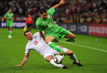 CAPE TOWN, SOUTH AFRICA - JUNE 18:  Jamie Carragher of England tackles Karim Matmour of Algeria during the 2010 FIFA World Cup South Africa Group C match between England and Algeria at Green Point Stadium on June 18, 2010 in Cape Town, South Africa.  (Pho