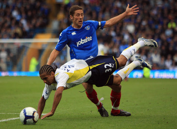 PORTSMOUTH, ENGLAND - OCTOBER 17:  Benoit Assou Ekotto of Tottenham Hotspur clashes with Michael Brown of Portsmouth during the Barclays Premier League match between Portsmouth and Tottenham Hotspur at Fratton Park on October 17, 2009 in Portsmouth, Engla