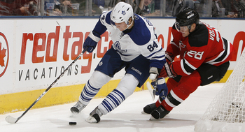 TORONTO - NOVEMBER 18: Mikhail Grabovski #84 of the Toronto Maple Leafs gets around Anton Volchenkov #28 of the New Jersey Devils during game action at the Air Canada Centre November 18, 2010 in Toronto, Ontario, Canada. (Photo by Abelimages/Getty Images)