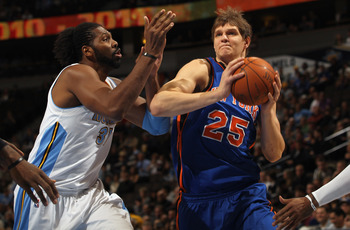 DENVER - NOVEMBER 16:  Timofey Mozgov #25 of the New York Knicks drives past Nene #31 of the Denver Nuggets at the Pepsi Center on November 16, 2010 in Denver, Colorado. NOTE TO USER: User expressly acknowledges and agrees that, by downloading and/or usin
