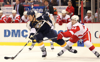 DETROIT - OCTOBER 30:  Darren Helm #43 of the Detroit Red Wings tries to check Shea Weber #6 of the Nashville Predators in a game on October 30, 2010 at the Joe Louis Arena in Detroit , Michigan. The Wings defeated the Predators 5-2. (Photo by Claus Ander