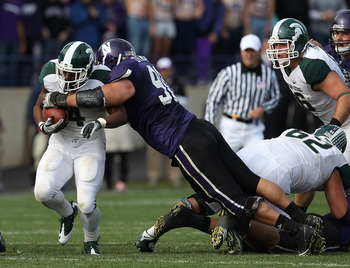 EVANSTON, IL - OCTOBER 23: Edwin Baker #4 of the Michigan State Spartans is tackled by Jack Di Nardo #90 of the Northwestern Wildcats at Ryan Field on October 23, 2010 in Evanston, Illinois. Michigan State defeated Northwestern 35-27. (Photo by Jonathan D