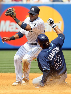NEW YORK - JULY 18:  Robinson Cano #24 of the New York Yankees is late with the tag as Carl Crawford #13 of the Tampa Bay Rays steals second base on July 18, 2010 at Yankee Stadium in the Bronx borough of New York City.  (Photo by Jim McIsaac/Getty Images