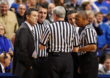 LEXINGTON, KY - JANUARY 02:  Rick Pitino (left) the Head coach of the Louisville Cardinals and John Calipari (right) the Head Coach of the Kentucky Wildcats talk with the game officals during the game against  at Rupp Arena on January 2, 2010 in Lexington