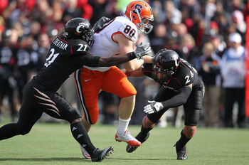 CINCINNATI - OCTOBER 30:  Nick Provo #80 of the Syracuse Orange runs with the ball while defended by Camerron Cheatham #21 and Wesley Richardson #24 of the Cincinnati Bearcats at Nippert Stadium on October 30, 2010 in Cincinnati, Ohio.  (Photo by Andy Lyo