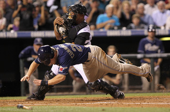 DENVER - SEPTEMBER 13:  Aaron Cunningham #28 of the San Diego Padres is tagged out at home by catcher Miguel Olivo #21 of the Colorado Rockies for the final out of the third inning as Cunningham tried to score on an Adrian Gonzalez base hit at Coors Field