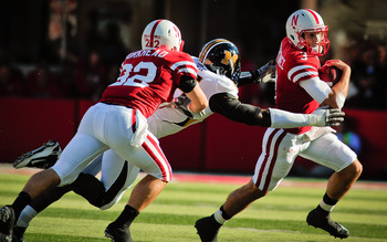 LINCOLN, NE - OCTOBER 30: Quarterback Taylor Martinez #3 of the Nebraska Cornhuskers runs from defensive end Aldon Smith #85 of the Missouri Tigers with help from  running back Rex Burkhead #22 during second half action of their game at Memorial Stadium o