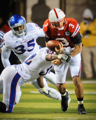 LINCOLN, NE - NOVEMBER 13: Taylor Martinez #3 of the Nebraska Cornhuskers gets the ball knocked from his arms by Steven Johnson #52 of the Kansas Jayhawks during second half action of their game at Memorial Stadium on November 13, 2010 in Lincoln, Nebrask