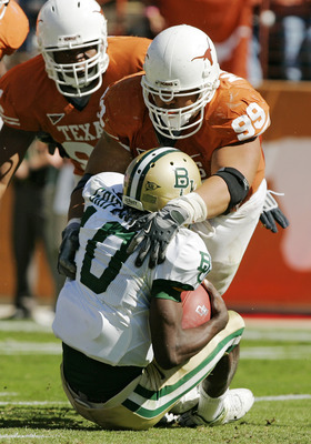 AUSTIN, TX - NOVEMBER 08:  Defensive tackle Roy Miller #99 of the Texas Longhorns sacks quarterback Robert Griffin #10 of the Baylor Bears in the second quarter on November 8, 2008 at Darrell K Royal-Texas Memorial Stadium in Austin, Texas.  (Photo by Bri
