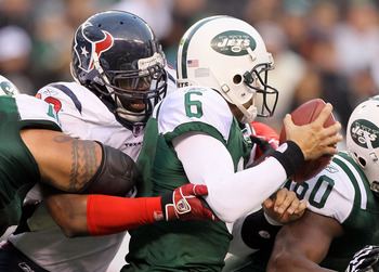 EAST RUTHERFORD, NJ - NOVEMBER 21: Mark Sanchez #6 of the New York Jets is sacked by Mario Williams #90 of the Houston Texans on November 21, 2010 at the New Meadowlands Stadium in East Rutherford, New Jersey. The Jets defeated the Texans 30-27.  (Photo b