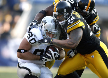 PITTSBURGH - DECEMBER 06:  Zach Miller #80 of the Oakland Raiders is tackled after a second quarter catch by LaMarr Woodley #56 of the Pittsburgh Steelers on December 6, 2009 at Heinz Field in Pittsburgh, Pennsylvania.  (Photo by Gregory Shamus/Getty Imag