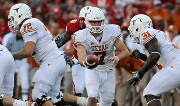 LINCOLN, NE - OCTOBER 16: Quarterback Garrett Gilbert #7 of the Texas Longhorns hand the ball to teammate running back Cody Johnson #31 during second half action of their game at Memorial Stadium on October 16, 2010 in Lincoln, Nebraska. Texas Defeated Ne