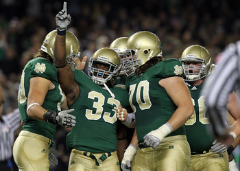 NEW YORK - NOVEMBER 20: Robert Hughes #33 of the Notre Dame Fighting Irish celebrates his touchdown with teammates agianst the Army Black Knights at Yankee Stadium on November 20, 2010 in the Bronx borough of New York City.  (Photo by Nick Laham/Getty Ima