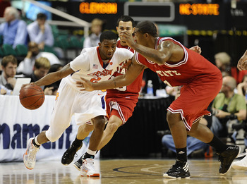 GREENSBORO, NC - MARCH 11:  Demontez Stitt #2 of the Clemson Tigers drives through Javier Gonzalez #10 and Richard Howell #1  of the NC State Wolfpack in their first round game in the 2010 ACC Men's Basketball Tournament at the Greensboro Coliseum on Marc