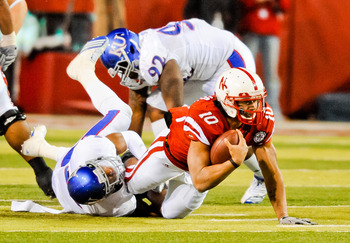 LINCOLN, NE - NOVEMBER 13: Roy Helu Jr. #10 of the Nebraska Cornhuskers is brought down by Isiah Barfield #19 of the Kansas Jayhawks during their game at Memorial Stadium on November 13, 2010 in Lincoln, Nebraska. Nebraska Defeated Kansas 20-3. (Photo by