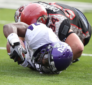 SALT LAKE CITY, UT - NOVEMBER 6: Ed Wesley #34 of the TCU Horned Frogs stretches the ball out after being tackled by Christian Cox #94 the Utah Utes during the second half of an NCAA Football game November 6, 2010 at Rice-Eccles Stadium in Salt Lake City,
