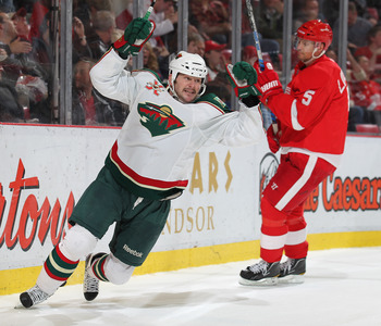 DETROIT,MI - NOVEMBER 19:  John Madden #11 of the Minnesota Wild celebrates his winning goal in overtime in a game against the Detroit Red Wings on November 19, 2010 at the Joe Louis Arena in Detroit, Michigan. The Wild defeated the Wings 4-3 in overtime.