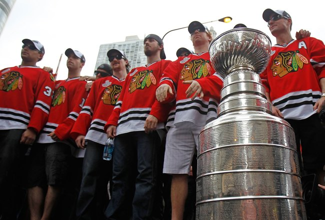 CHICAGO - JUNE 11: Members of the Chicago Blackhawks stand with the Stanley Cup during the Chicago Blackhawks Stanley Cup victory parade and rally on June 11, 2010 in Chicago, Illinois. (Photo by Jonathan Daniel/Getty Images)