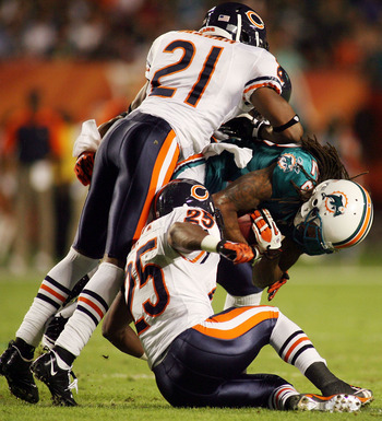 MIAMI - NOVEMBER 18:  Receiver Davone Bess #15 of the Miami Dolphinsis tackled by Corey Graham #21 and Garrett Wolfe #25 of the Chicago Bears at Sun Life Stadium on November 18, 2010 in Miami, Florida.  (Photo by Marc Serota/Getty Images)