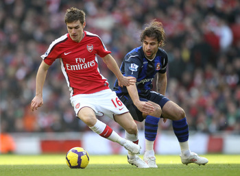 LONDON, ENGLAND - FEBRUARY 20:  Aaron Ramsey of Arsenal holds off Lorik Cana of Sunderland during the Barclays Premier League match between Arsenal and Sunderland at the Emirates Stadium on February 20, 2010 in London, England.  (Photo by Julian Finney/Ge