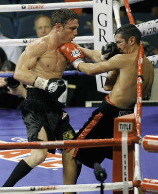LAS VEGAS - SEPTEMBER 19:  Michael Katsidis (R) trades punches with Vincent Escobedo during their WBO interim lightweight title fight at the MGM Grand Garden Arena September 19, 2009 in Las Vegas, Nevada. Katsidis won by split decision.  (Photo by Eric Ja