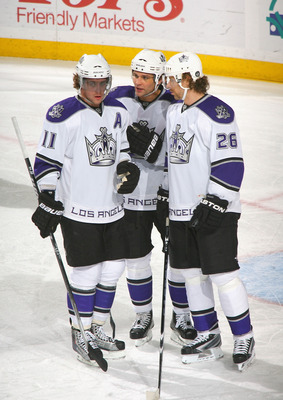 BUFFALO, NY - NOVEMBER 19: Anze Kopitar #11, Davis Drewiske #44, and Michal Handzus #26 of the Los Angeles Kings talk during a stoppage in play against the Buffalo Sabres at HSBC Arena on November 19, 2010 in Buffalo, New York.  (Photo by Rick Stewart/Get
