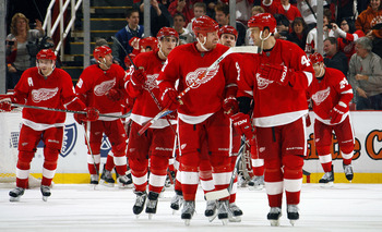 DETROIT - NOVEMBER 21:  Johan Franzen #93 and teammate Todd Bertuzzi #44 of the Detroit Red Wings lead their team off the ice as they celebrate a come from behind overtime victory during their NHL game at Joe Louis Arena on November 21, 2010 in Detroit, M