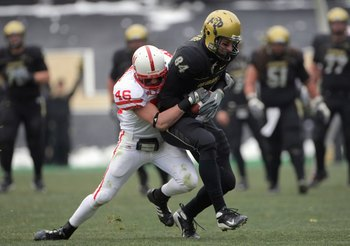 BOULDER, CO - NOVEMBER 23: Tyson DeVree #84 of the Colorado Buffaloes carries the ball as he is grabbed by Ben Eisenhart #46 of the Nebraska Cornhuskers during Big 12 College Football action at Folsom Field on November 23, 2007 in Boulder, Colorado. Color