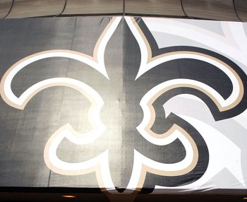 NEW ORLEANS - SEPTEMBER 23:  A pedestrian walks past a giant Fleur-de-Lis outside the Louisiana Superdome as it prepares to reopen on September 23, 2006 in New Orleans, Louisiana.  The Superdome will reopen for the first NFL New Orleans Saints game agains