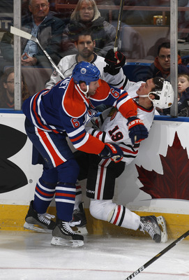 EDMONTON, CANADA - NOVEMBER 17:  Ryan Whitney #6 of the Edmonton Oilers checks Jonathan Toews #19 of the Chicago Blackhawks in first-period action at Rexall Place November 5, 2010 in Edmonton, Alberta, Canada. (Photo by Dale MacMillan/Getty Images)