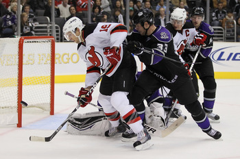 LOS ANGELES, CA - OCTOBER 30:  Travis Zajac #19 of the New Jersey Devils tips the puck wide of the net while being checked by Willie Mitchell #33 of the Los Angeles Kings in the third period at Staples Center on October 30, 2010 in Los Angeles, California