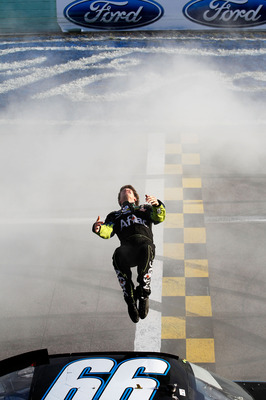 HOMESTEAD, FL - NOVEMBER 21:  Carl Edwards, driver of the #99 Aflac Ford, performs a back flip to celebrate winning the NASCAR Sprint Cup Series Ford 400 at Homestead-Miami Speedway on November 21, 2010 in Homestead, Florida.  (Photo by Todd Warshaw/Getty