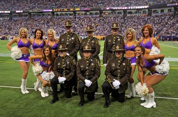 MINNEAPOLIS - OCTOBER 18:  The Minnesota Vikings cheerleaders pose for a photo with members of the Sherburne County Sheriffs Department as the Vikings face the Baltimore Ravens during NFL action at Hubert H. Humphrey Metrodome on October 18, 2009 in Minne