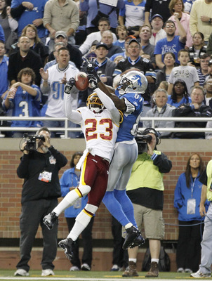 DETROIT - OCTOBER 31:  DeAngelo Hall #23 of the Washingon Redskins intercepts the pass during the second quarter as Calvin Johnson #81 of the Detroit Lions atempts to defend during the game at Ford Field on October 31, 2010 in Detroit, Michigan.  (Photo b